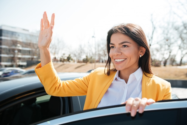 Femme d'affaires réussie, debout près de la voiture et en agitant la main