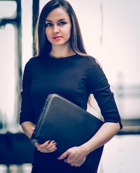 Femme d'affaires réussie avec des documents sur le fond d'un