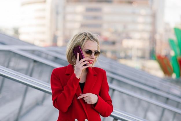 Femme d'affaires réussie en manteau rouge parler sur smartphone négocier un accord sur le fond des immeubles élevés dans le centre d'affaires.