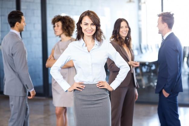 Femme d'affaires réussie souriant pendant que ses collègues interagissent les uns avec les autres
