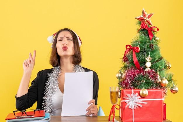 Femme d'affaires de rêve en costume avec chapeau de père noël et décorations de nouvel an travaillant seul pointant au-dessus et assis à une table avec un arbre de noël dessus dans le bureau