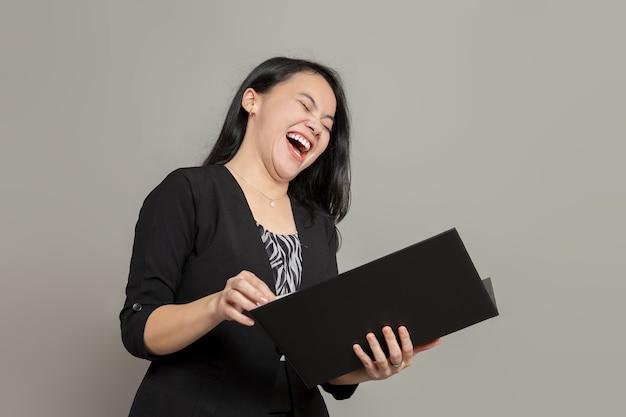Femme d'affaires en riant tout en maintenant le dossier
