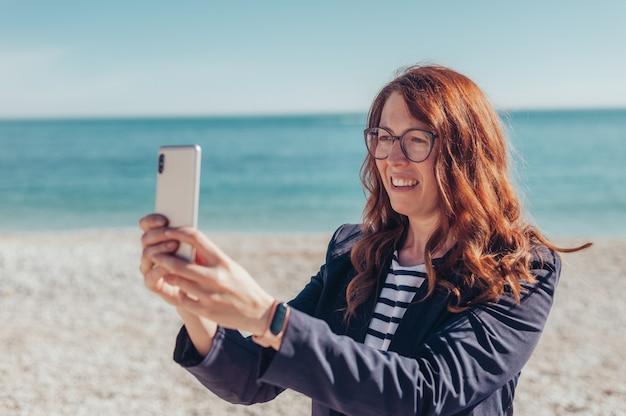 Femme d'affaires rousse à l'aide de téléphone au bord de la mer
