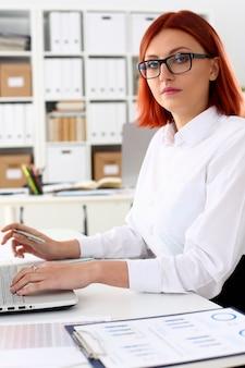 Femme affaires, rousse, bureau, portrait, asseoir, table
