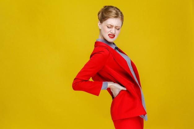 Une femme d'affaires rousse en costume rouge a mal aux reins ou au dos