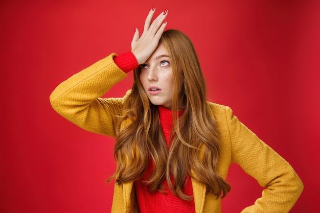 Une femme d'affaires rousse faisant un geste de facepalm avec la main sur le front en levant les yeux d'agacement et d'irritation comme étant choquée par la façon dont le client stupide soupire dérangé par le mur rouge, fatigué.