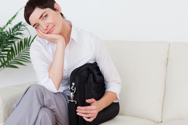 Femme d'affaires s'ennuie assis sur un canapé