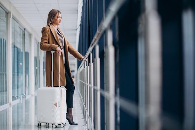 Femme d'affaires avec sac de voyage à l'aéroport