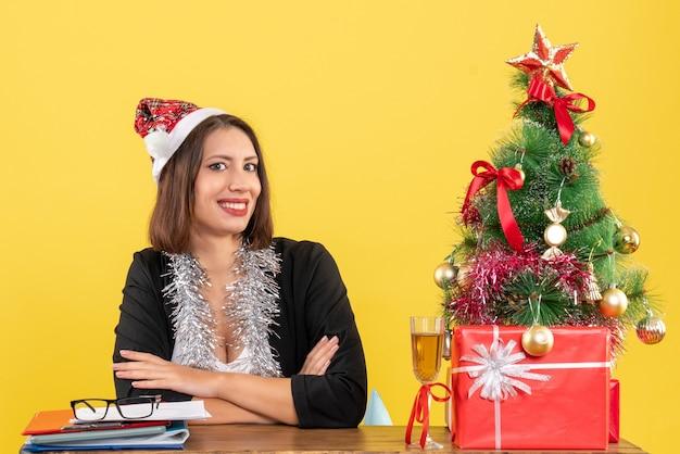 Femme d'affaires satisfaite en costume avec chapeau de père noël et décorations de nouvel an tenant des documents et assis à une table avec un arbre de noël dessus dans le bureau
