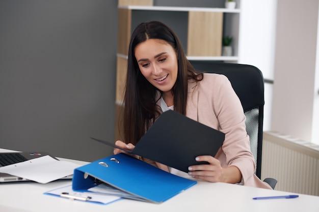 Une femme d'affaires satisfaite et excitée célébrant le succès commercial motivé par un excellent travail financier se traduit par un rapport, une lettre de lecture d'un employé joyeux ou un avis avec de bonnes nouvelles heureux de la promotion de l'emploi