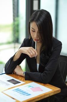 Femme d'affaires se concentrant et réfléchissant à son plan de travail budgétaire avec des rapports financiers au bureau