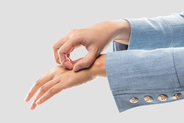 Femme d'affaires se grattant le dos de la main à cause des démangeaisons causées par l'irritation.