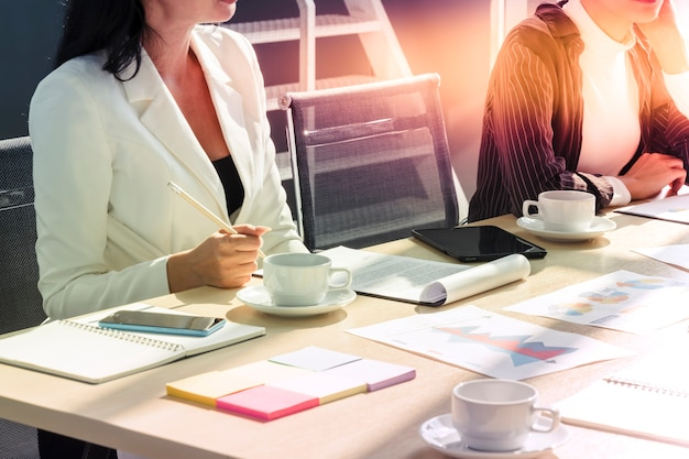 Une femme d'affaires se joint à la conférence de réunion avec du papier et une tablette sur une table de bureau moderne