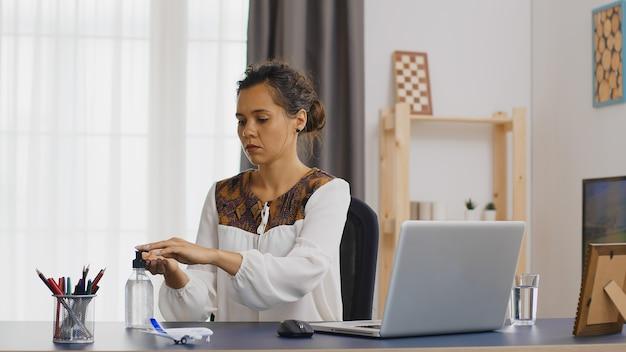 Femme d'affaires se lavant les mains avec un désinfectant tout en travaillant à domicile.
