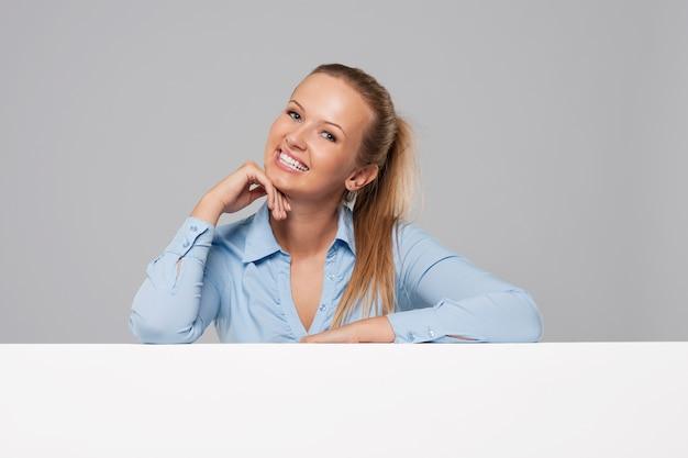 Femme d'affaires se penchant sur une pancarte vierge