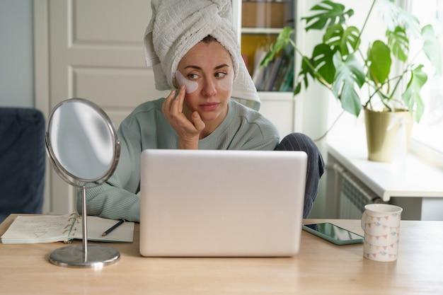 Une femme d'affaires se prépare pour une vidéoconférence sur un ordinateur portable avec des patchs et une serviette sur les cheveux le matin