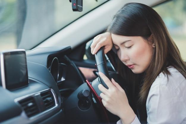 Femme d'affaires se sentir essayé de dormir dans une voiture