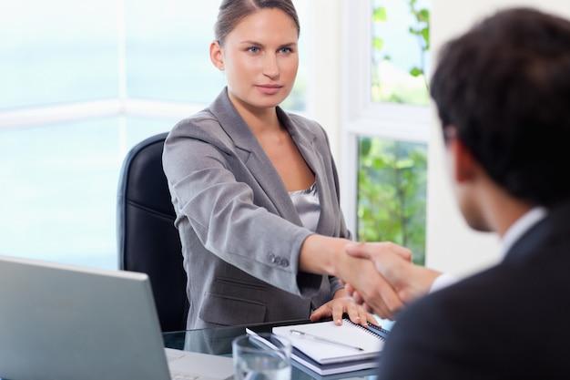 Femme d'affaires se serrant la main avec le client