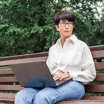 Femme affaires, séance banc, et, regarder loin