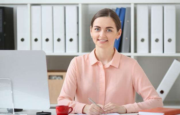 Femme affaires, séance, bureau, table, regarder, appareil photo, tenue, stylo, main