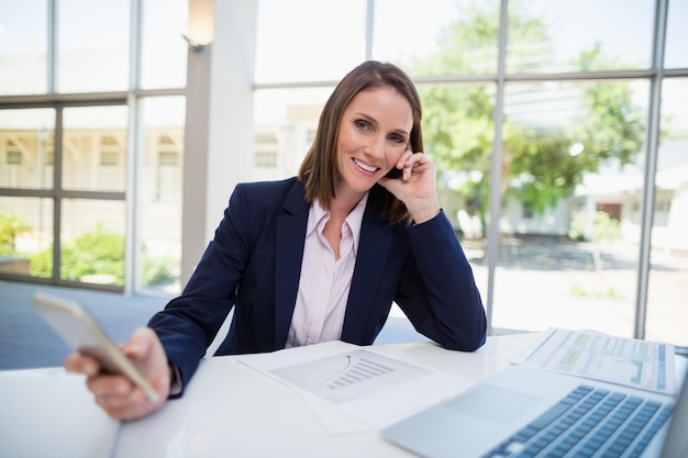 Femme affaires, séance bureau, et, utilisation, téléphone portable