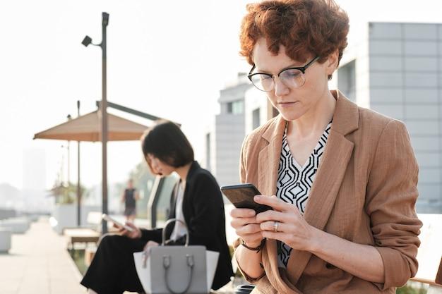 Femme affaires, séance, dehors, utilisation, smartphone