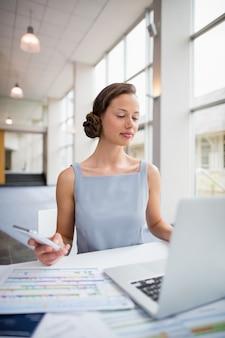 Femme affaires, séance, ordinateur portable, utilisation, mobile ...