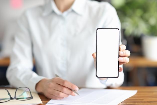 Femme affaires, séance table, à, documents, et, projection, téléphone mobile, gros plan