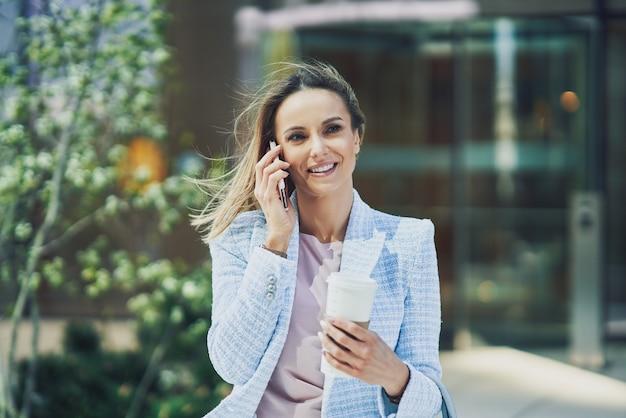 Femme d'affaires séduisante adulte avec smartphone et café marchant dans la ville. photo de haute qualité