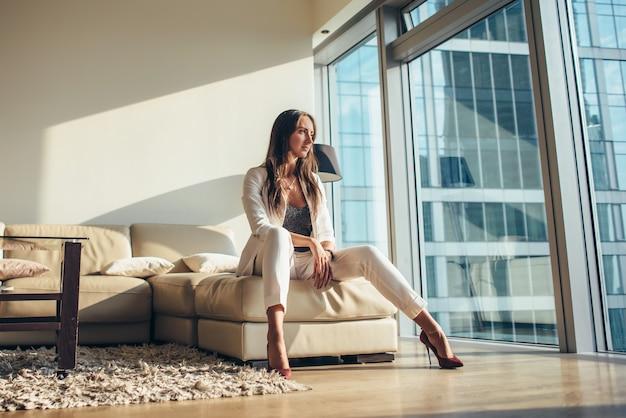 Femme d'affaires séduisante portant des vêtements de bureau formels assis dans une posture séduisante sur un canapé dans un appartement moderne.