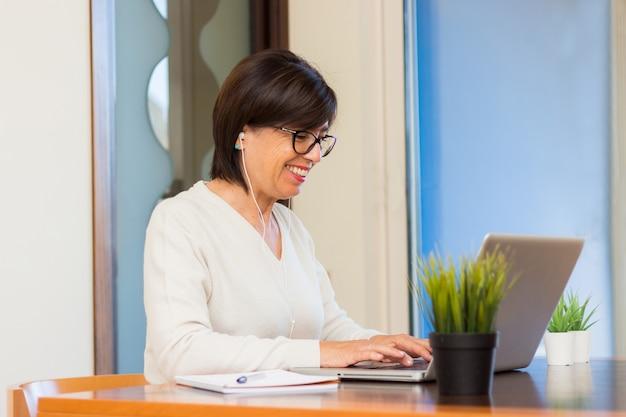 Femme d'affaires senior à l'aide d'un ordinateur portable à la maison