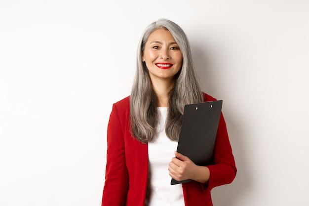 Femme d'affaires senior asiatique réussie tenant un presse-papiers, portant un blazer rouge et du rouge à lèvres au travail, souriant à la caméra, fond blanc