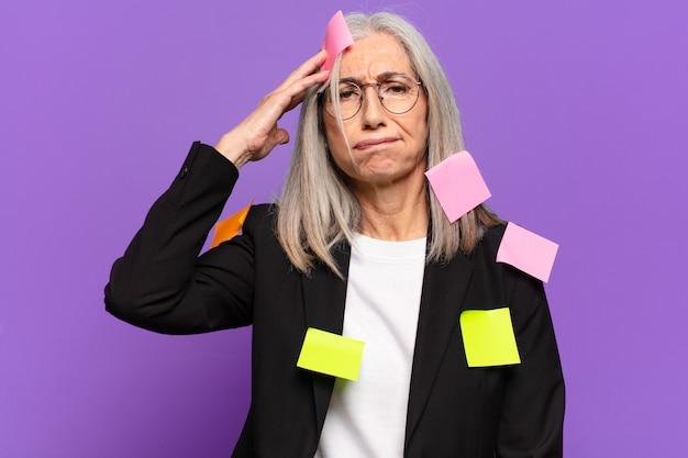 Femme d'affaires senior avec poste adhésif.