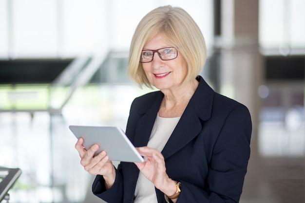 Une femme d'affaires senior réussie utilisant le pavé tactile