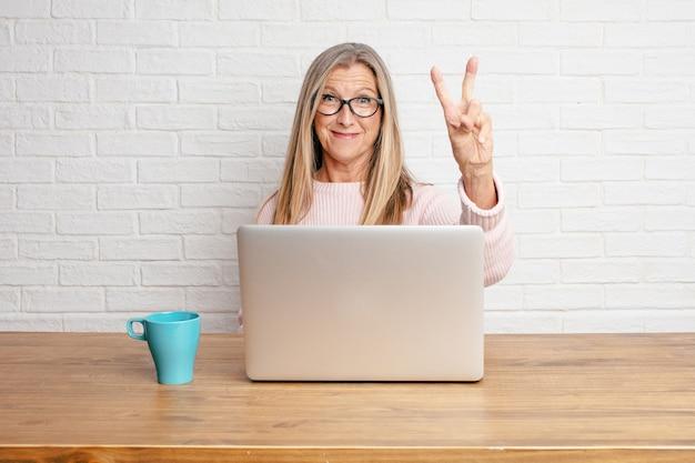 Femme d'affaires senior souriant et à la recherche de satisfaction et de bonheur, comptant le numéro deux avec les doigts.