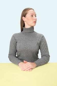 Femme d'affaires sérieuse assise à table sur l'espace bleu