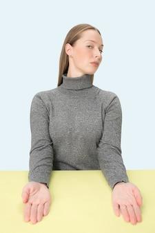 Femme d'affaires sérieuse assise à table sur un fond de studio rose. le portrait dans un style minimalisme