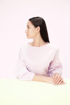 Femme d'affaires sérieuse assise à table sur un studio rose.