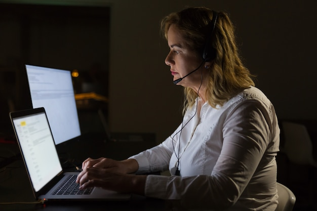 Femme d'affaires sérieuse en casque tapant sur ordinateur portable