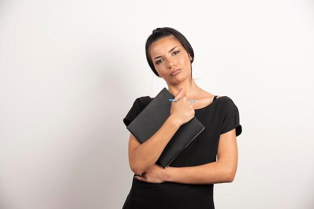 Femme d'affaires sérieuse avec ordinateur portable posant sur un mur blanc.