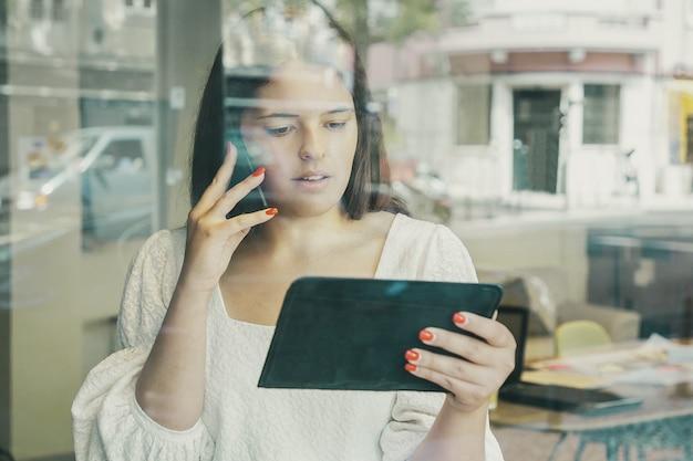 Femme d'affaires sérieuse parlant sur cellule, à l'aide de tablette et regardant l'écran