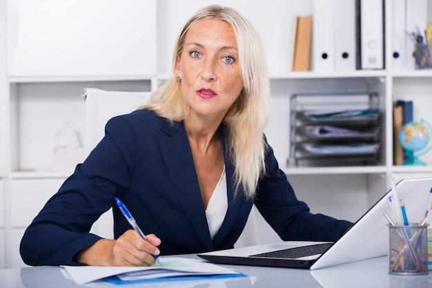 Femme d'affaires sérieuse travaillant au bureau