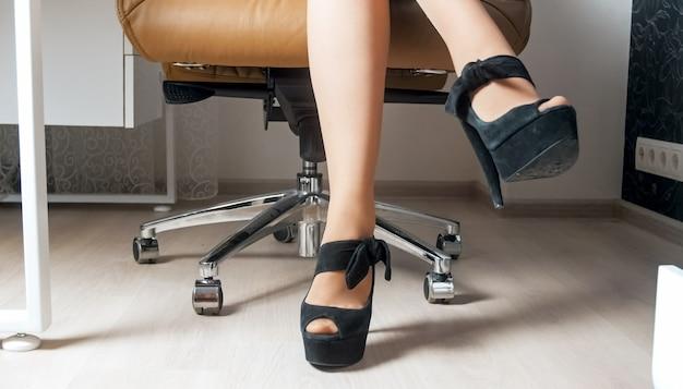 Femme d'affaires sexy en collants et chaussures à talons hauts assis dans un fauteuil de bureau.