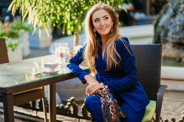Femme d'affaires sexy portant un costume bleu assis dans un café d'été