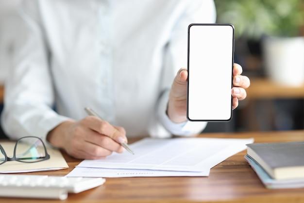 La femme d'affaires signe le contrat et tient le smartphone avec l'écran blanc