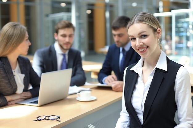 Femme d'affaires avec son personnel, groupe de personnes en arrière-plan dans un bureau moderne et lumineux à l'intérieur.