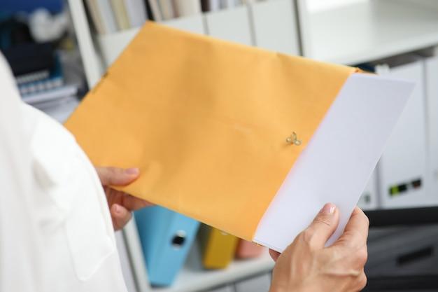La femme d'affaires sort des documents de l'enveloppe jaune recevant le concept de courrier d'affaires