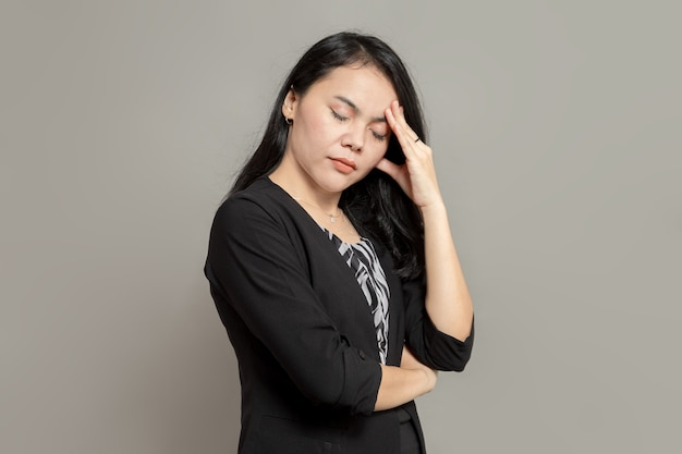 Femme d'affaires a souligné l'expression tout en tenant sa tête et en fermant les yeux