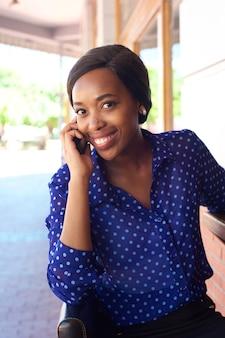 Femme d'affaires souriant à l'aide de téléphone portable