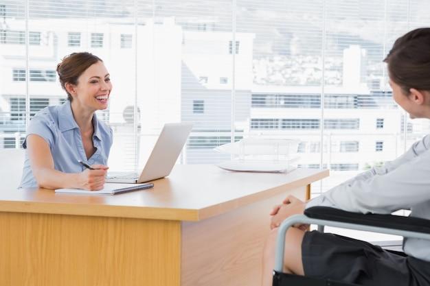 Femme d'affaires souriant à un candidat à un emploi handicapé